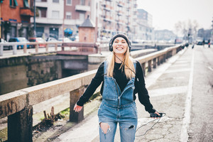 Knee figure of young beautiful blonde straight hair woman in the city listening music with headphones, laughing - music, having fun, happiness concept
