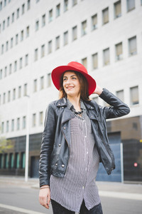 Knee figure of young beautiful brunette eastern girl walking in the suburbs overlooking right dressed with red hat, pair of black jeans and striped black and white shirt - carefreeness, youth concept