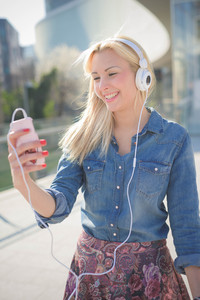 Knee figure of young beautiful caucasian blonde girl listening to music in the city with headphones smiling overlooking right - relax, youth, emancipation concept