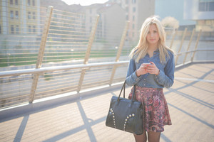 Knee figure of young beautiful caucasian blonde girl using a smartphone wearing a jeans shirt, a bag and a floral skirt looking downward the screen - technology, communication, social network concept