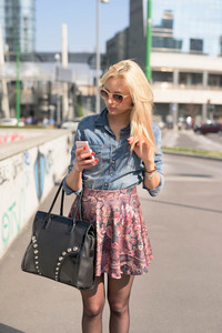 Knee figure of young beautiful caucasian blonde girl walking through the streets using smartphone - technology, communications, social network concept - wearing jeans shirt and floral skirt