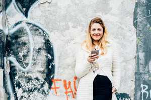 Knee figure of young beautiful caucasian blonde hair woman leaning on concrete wall listening music with earphones and smart phone hand hold, looking at camera, smiling - happiness, music, relax concept