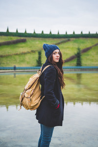 Knee figure of young beautiful caucasian long brown hair woman wearing backpack looking at camera, serene - pensive, thinking future, melancholy concept