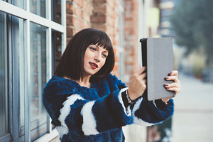 Knee figure of young beautiful eastern brown hair woman leaning against a wall, looking down and tapping the screen of a tablet hand hold - technology, social network, business concept