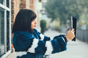 Knee figure of young beautiful eastern brown hair woman outdoor in the city, taking selfie with tablet hand hold - technology, social network, business concept