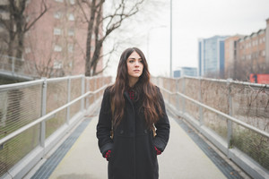Knee figure of young beautiful long hair serious and pensive woman living the city in winter outdoor - concept of humans emotions - dressed with black coat and checked red shirt