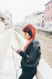 Knee figure of young beautiful red hair venezuelan woman outdoor in the city listening music with headphones and smart phone han hold - technology, music, social network concept