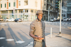 Knee figure of young handsome afro black man in city sunset holding a smartphone, looking downward the screen - technology, social network, communication concept