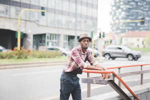 Knee figure of young handsome afro black man leaning against an handrail wearing jeans overalls and checked shirt, looking in camera, pensive - thoughtful, thinking future concept
