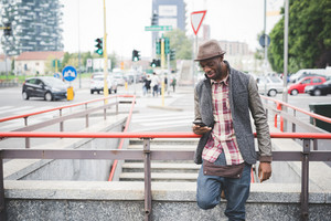 Knee figure of young handsome afro black man leaning on a handrail, holding a smartphone, looking downward the screen smiling- technology, social network, communication concept