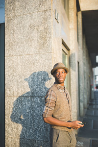 Knee figure of young handsome afro black man posing leaning against a wall, holding a smartphone, overlooking right - technology, social network, communication concept