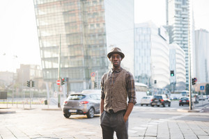 Knee figure of young handsome afro black man posing outside in the city, hands in pocket looking in camera, serious - pensive, thoughtful, thinking future concept