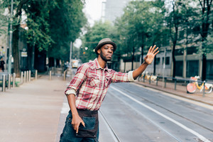 Knee figure of young handsome afro black man trying to call a taxi raising his hand in the city, overlooking left - transport concept