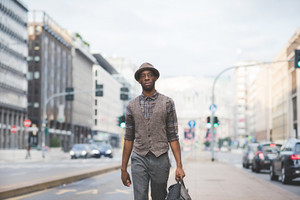Knee figure of young handsome afro black man walking in the street of the city, holding a bag, overlooking left, pensive - thoughtful, thinking future concept
