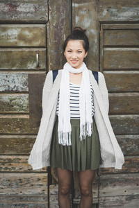 Knee figure of young handsome asiatic chinese woman posing against a front door, looking in camera smiling, hands in pocket - youth, happiness, carefree concept
