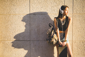 Knee figure of young handsome asiatic long brown straight hair woman listening music with headphones, holding a backpack and a skateboard, overlooking left - technology, sportive concept