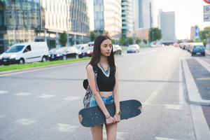 Knee figure of young handsome asiatic long brown straight hair woman skater listening music with earphones, overlooking right, pensive - thinking future, serious, thoughtful concept