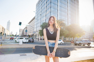 Knee figure of young handsome asiatic long brown straight hair woman skater posing in the city, looking in camera, pensive - sportive, thoughtful, seriousness concept