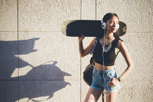 Knee figure of young handsome asiatic skater woman listening music with headphones, leaning against a wall, holding skate on her shoulder, overlooking left - music, technology, sportive concept