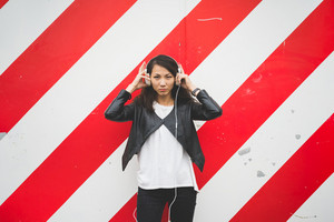 Knee figure of young handsome asiatic woman leaning against striped red and white wall, putting on her headphones, looking in camera, serious - music, thoughtful concept