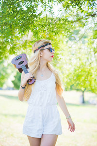 Knee figure of young handsome caucasian long blonde straight hair hippy woman walking in a city park holding an ukulele, overlooking left - music, artist concept