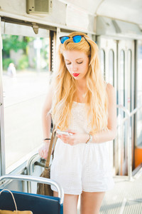 Knee figure of young handsome caucasian long blonde straight hair woman on a bus, using smartphone, looking downward and tapping the screen - technology, social network, communication concept