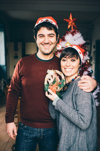 Knee figure of young handsome caucasian man and woman couple holding and showing a crown decoration, looking in camera, smiling - christmas, celebration, love concept