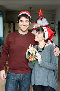Knee figure of young handsome caucasian man and woman couple holding and showing a crown decoration, looking in camera, smiling  - christmas, couple concept