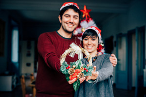 Knee figure of young handsome caucasian man and woman couple holding and showing a crown decoration, looking in camera, smiling - focus on the crown decoration - christmas, couple concept