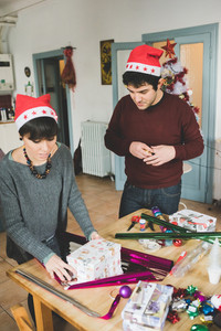 Knee figure of young handsome caucasian man and woman couple wrapping christmas present with wrapping paper and ribbon, both looking downward - christmas, couple, holiday concept