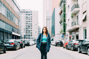 Knee figure of young handsome caucasian reddish straight hair woman posing on the middle of the street, hands in pocket, loooking upward, pensive - thoughtful, thinking future concept