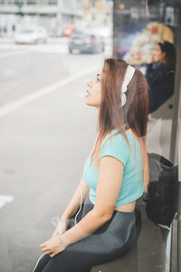 Knee figure of young handsome caucasian reddish straight hair woman sitting at the bus stop listening music with headphones, looking straight, pensive - thinking future, thoughtful concept