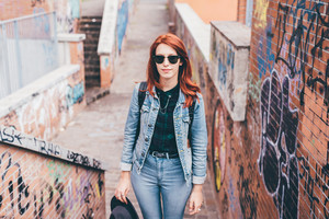 Knee figure of young handsome caucasian redhead straight hair woman posing on a staircase in the city, wearing sunglasses, looking in camera pensive - serious, thoughtful concept