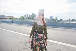 knee figure of young handsome caucasian redhead woman with headphones around neck, smartphone handheld, overlooking right, smiling - relaxing, carefreeness concept - wearing green shirt, floral skirt