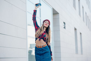 Knee figure of young handsome caucasian woman listening music with headphones and smartphone handhold feeling free with arms wide open - freedom, music, technology concept