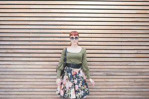 Knee figure of young handsome redhead caucasian woman, leaning against a wall, looking in camera, smiling - pin up, carefreeness concept - wearing green shirt, floral skirt, bag and sunglasses