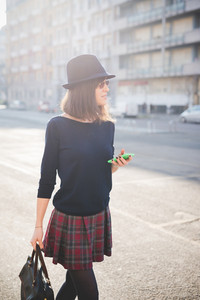 knee figure of young pretty brown hair woman walking trough the streets using smartphone, overlooking left, dressed with checked skirt, black sweater and hat - technology, social network concept