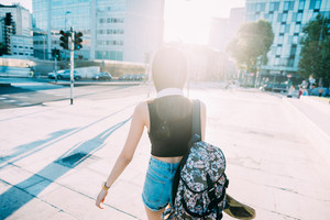 Knee figure rear view of young beautiful asiatic woman walking outdoor in the city back light with backpack and skate - traveler, skater, thinking future concept