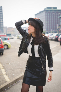 Knee figureof a young beautiful caucasian brown hair girl posing in the city looking in camera - Freshness, serene, carefreeness concept - dressed with white shirt, black jacket and hat