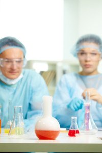 Laboratory bottle with chemical substance during experiment with two chemists on background