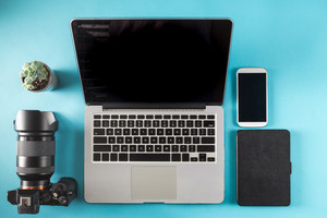 Laptop, camera, smartphone and tablet on a blue background