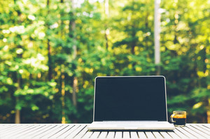 Laptop computer outside with a forest background