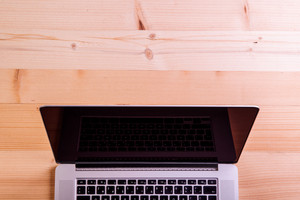 Laptop layid on office desk. Studio shot on wooden background. Copy space