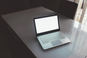 Laptop with black screen on table - business, technology concept