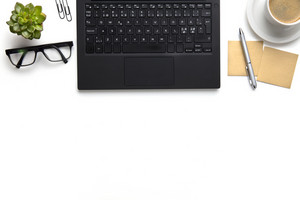 Laptop With Eyeglasses, Coffee Cup And Notes On White Desk