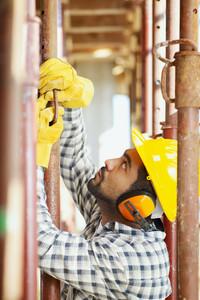 latin american construction worker fastening girder. Side view