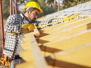 latin american construction worker on house roof with measuring tape. Copy space