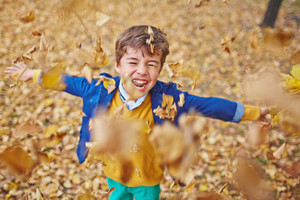 Laughing boy playing with falling leaves in park