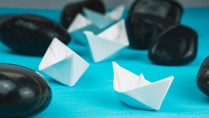 Leadership white paper boat lead further ships between abstract rock stones on blue background. Vintage Look