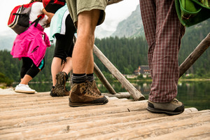 Leg of unrecognizable people standing on wooden bridge, at the lake in the mountains